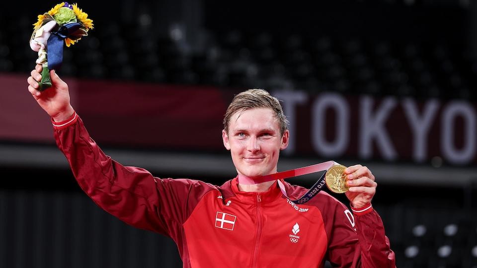 Il tient sa médaille d'or.