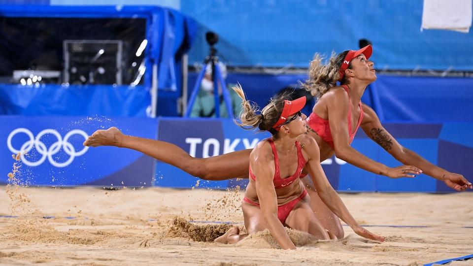 Deux joueuses de volleyball de plage plongent pour toucher au ballon.