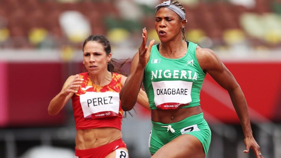 La sprinteuse court, les yeux fermés, bien concentrée pendant un 100 mètres. Elle porte un maillot vert et devance son adversaire espagnole, en rouge.