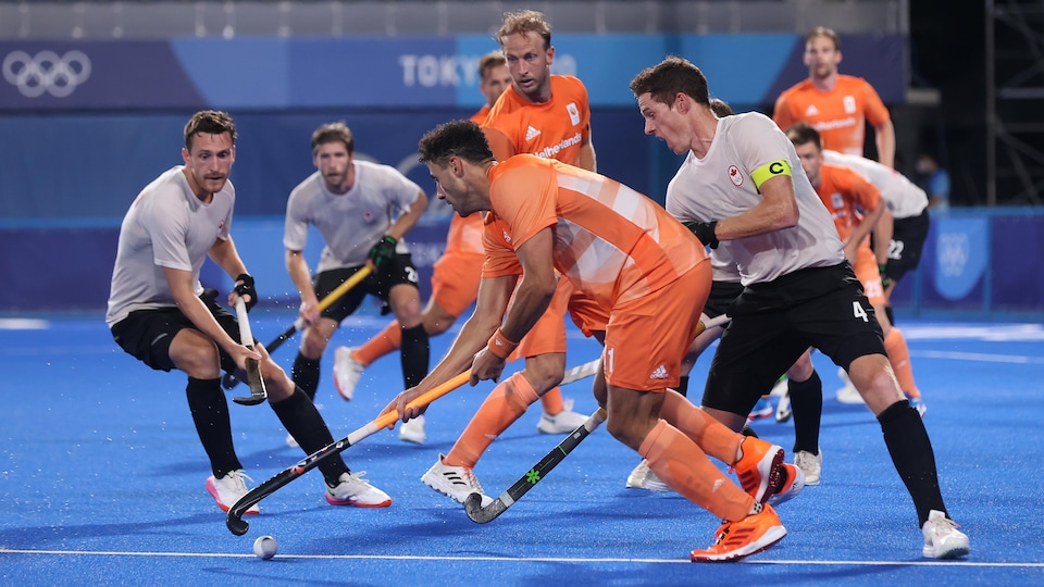 Un joueur des Pays-Bas tentent de déjouer deux défenseurs canadiens.