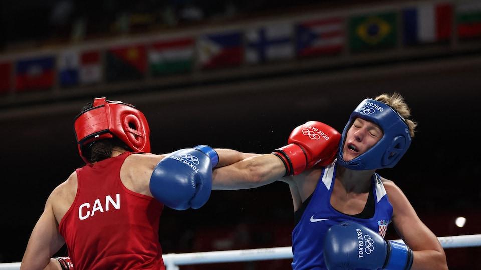 Une boxeuse en rouge frappe durement son adversaire, en bleu, de la droite pendant un combat.