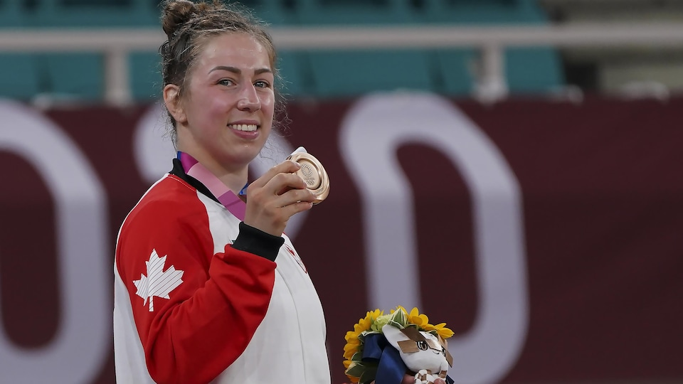 Catherine Beauchemin-Pinard tient sa médaille de bronze de la main droite et des fleurs dans sa main gauche.
