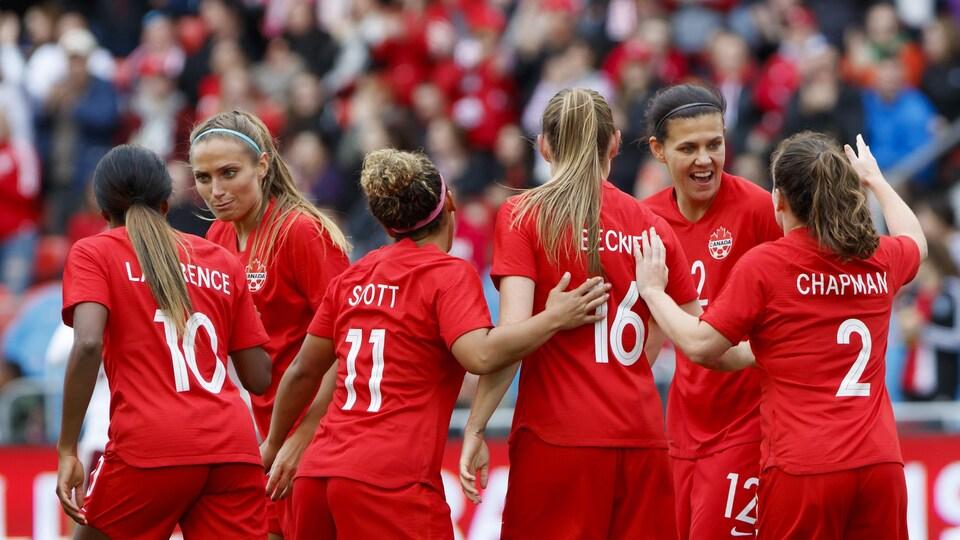 Christine Sinclair célèbre un but sur le terrain avec des coéquipières de l'équipe féminine canadienne de soccer.