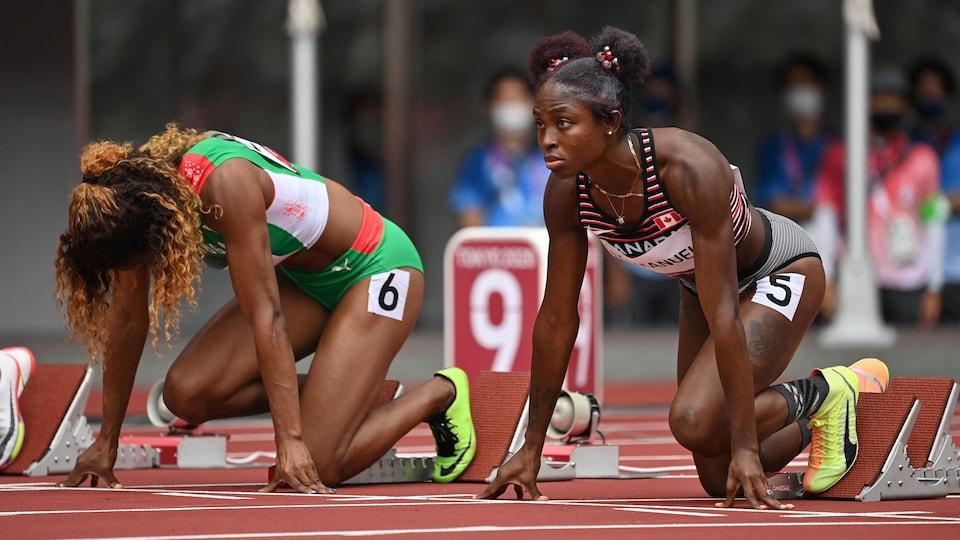 Elle est dans les blocs de départ avec une autre athlète.