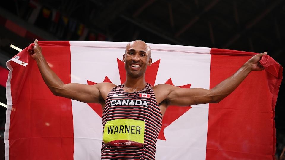Il tient le drapeau canadien après sa victoire.