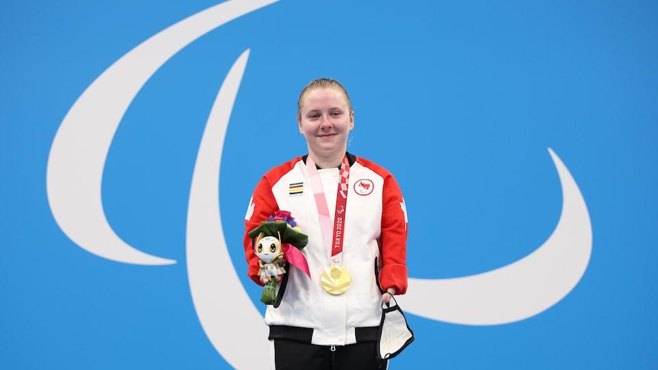 Danielle Dorris se tient sur le podium avec sa médaille d'or et son bouquet.
