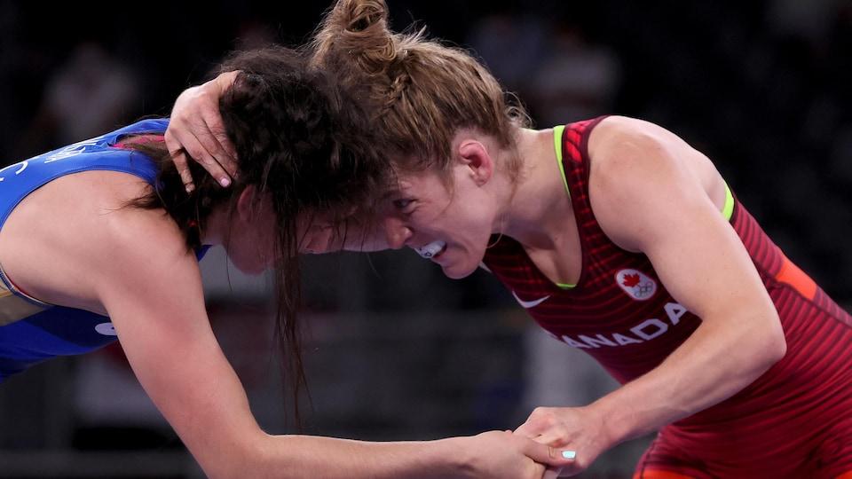 Deux lutteuses se collent la tête pendant qu'une d'entre elles tient celle de son adversaire et agrippe sa main droite.