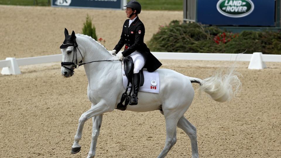 La cavalière canadienne Colleen Loach dirige son cheval  pour effectuer les enchaînements de pas, tel un ballet pour impressionner les juges.