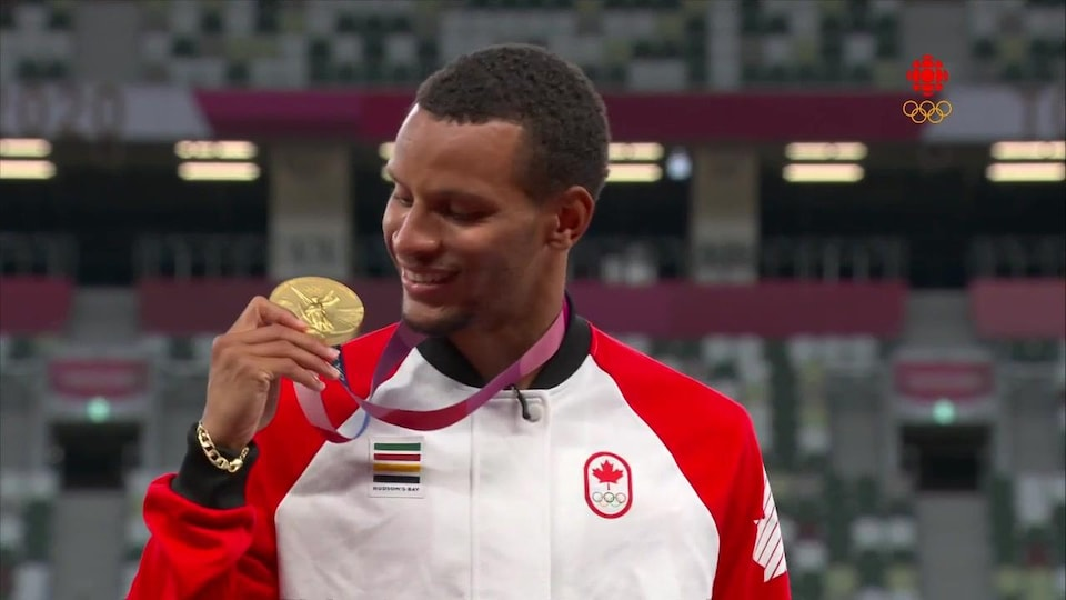 Andre De Grasse sur le podium regarde sa médaille d'or.