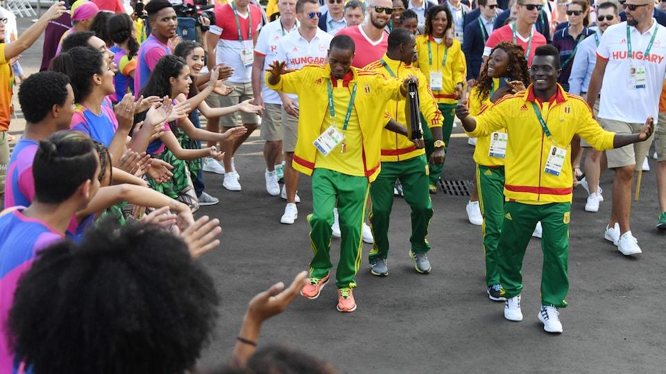 Cinq membres de la délégation guinéenne défilent en dansant.
