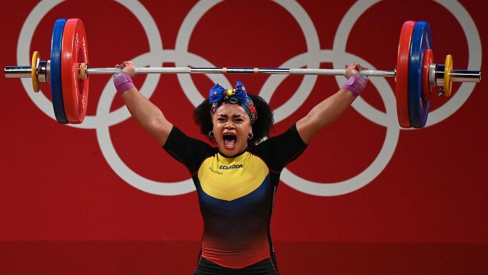 Une haltérophile hurle de joie en soulevant la barre.