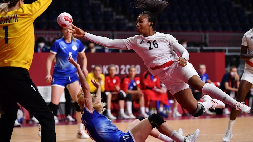 Une joueuse de handball vole dans les airs pendant qu'elle effectue un tir sur la gardienne adverse et qu'une rivale tombe au sol.