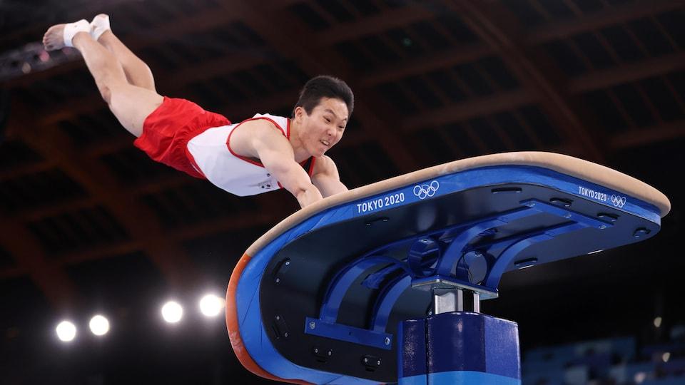 Le Sud-Coréen met ses mains sur la table de saut pour se propulser.