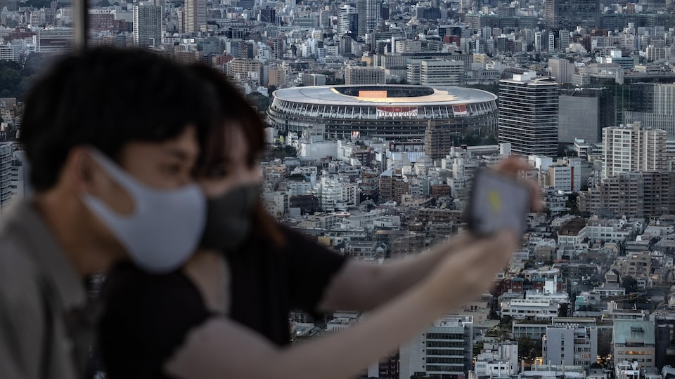 Deux jeunes Japonais prennent un égoportrait avec, en arrière-plan, le stade olympique de Tokyo.