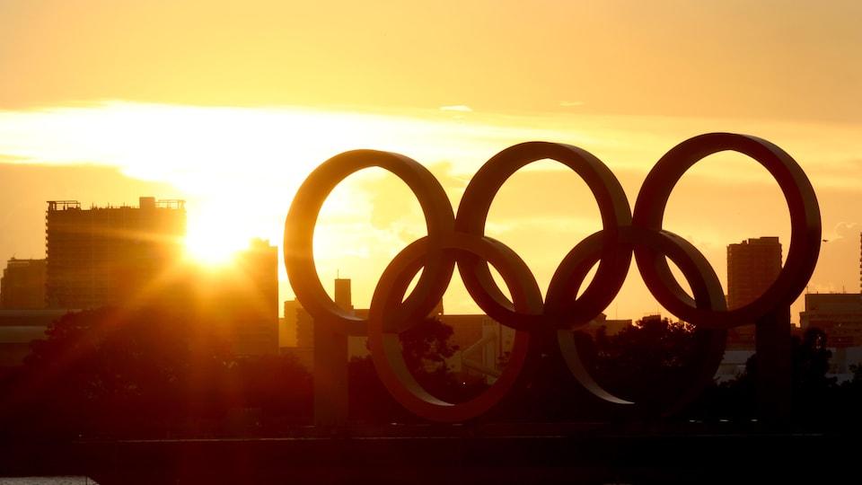 Un coucher de soleil à travers les anneaux olympiques près d'un plan d'eau