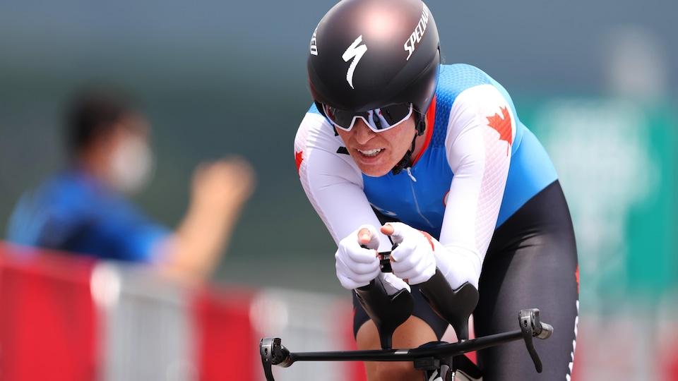 Une jeune femme participe a une épreuve de vitesse sur vélo. Elle porte un chandail bleu et blanc avec une feuille d'érable et un casque noir avec des lunettes de soleil.