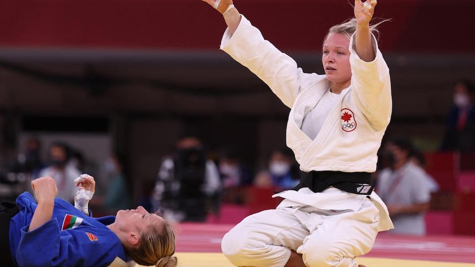 Agenouillée, la judoka canadienne lève les bras au ciel alors que son adversaire bulgare est étendue au sol à côté.