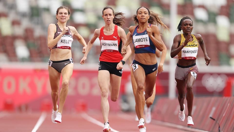 Cinq jeunes femmes courent avec vigueur pour atteindre le fil d'arrivée.