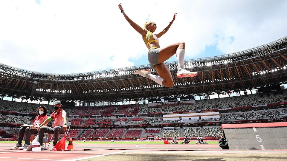 Une athlète au saut en longueur est dans les airs et s'apprête à atterrir dans le sable. Elle s'exécute devant des gradins vides.