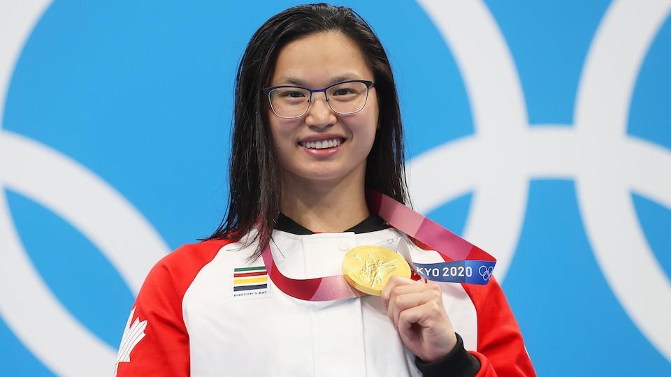 Margaret Mac Neil montre sa médaille d'or devant le logo olympique.