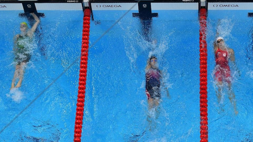 Trois nageuses en action terminent leur course.