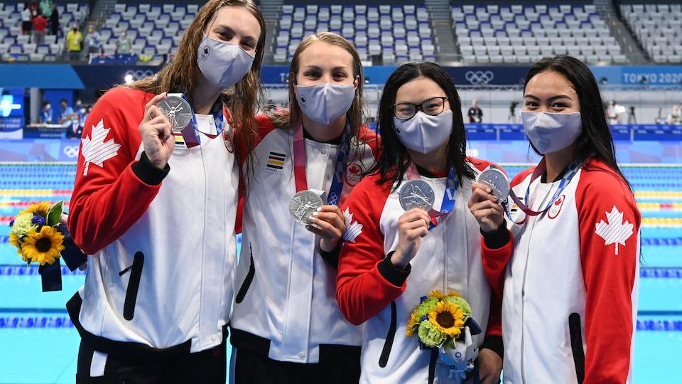 Des athlètes avec un manteau aux couleurs du Canada montrent une médaille sur le bord de la piscine.