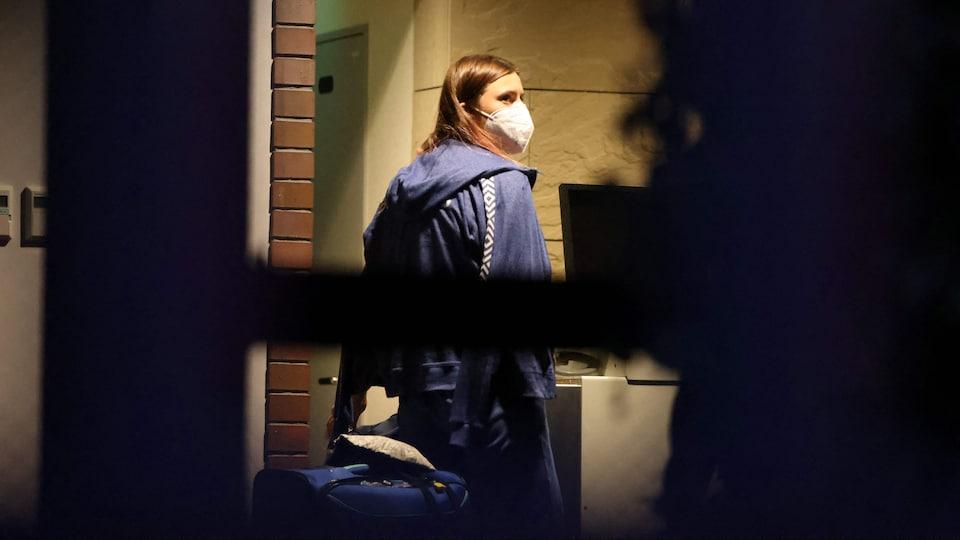 La sprinteuse est à l'extérieur de l'ambassade polonaise à Tokyo avec sa valise à la main.