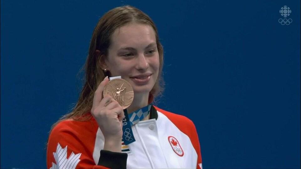 La nageuse canadienne affiche un grand sourire avec sa médaille de bronze dans sa main droite, lors de la cérémonie de remise de médailles du 200 m style libre.