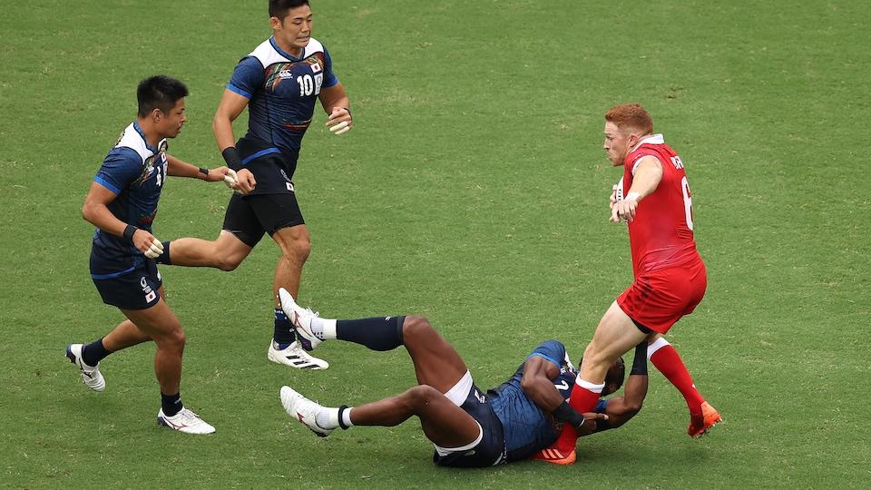 Il freine devant des adversaires alors que l'un d'eux s'accroche à ses jambes.