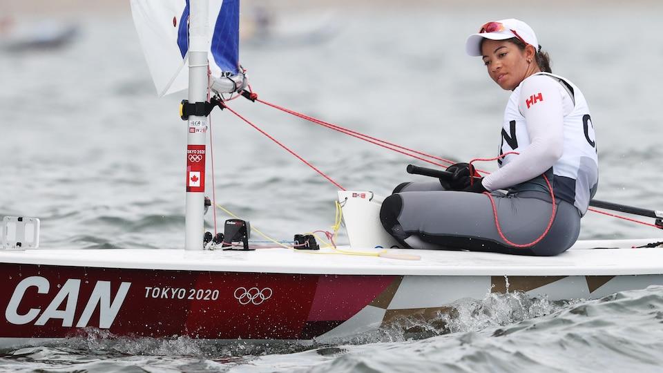 Une athlète de voile est aux commandes de son bateau.