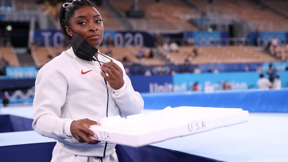La gymnaste retire son masque. On voit des gradins vides à l'arrière.