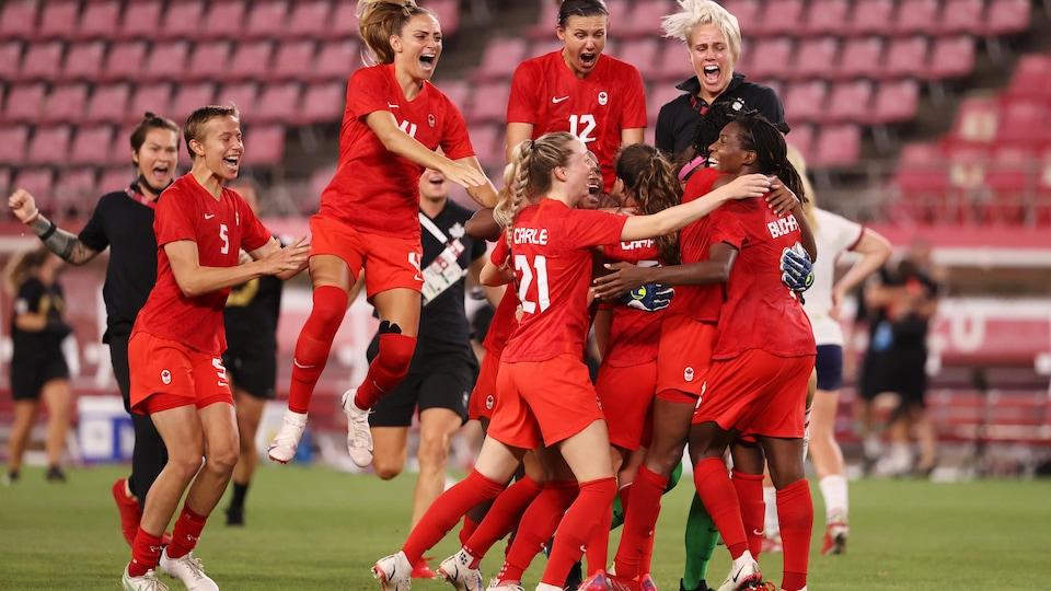 Des joueuses de soccer se sautent dans les bras, rient et sourient.