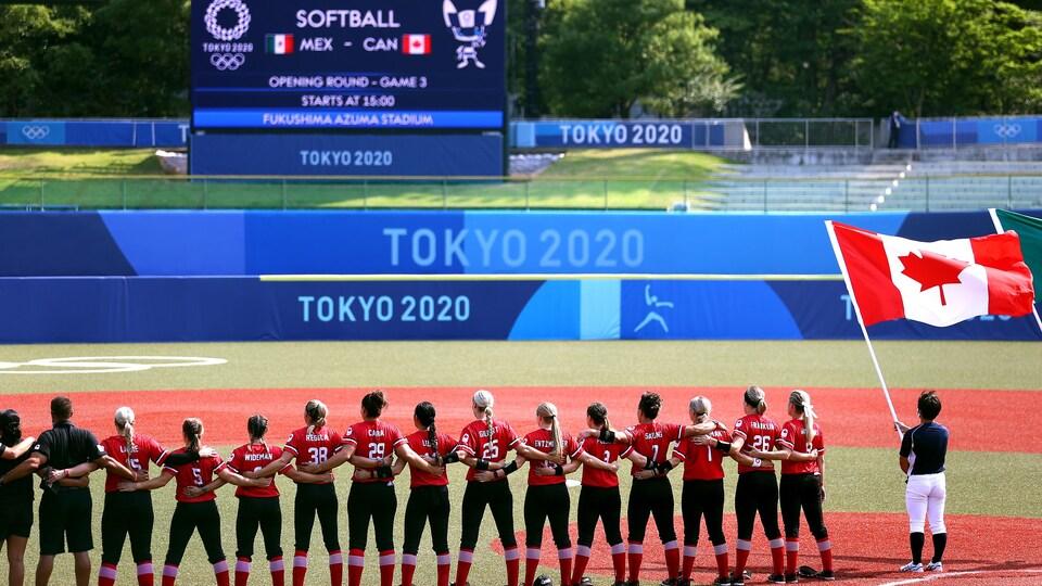 L'équipe féminine canadienne de softball pendant l'hymne national avant le début de son premier match.