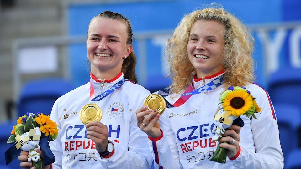 Les deux joueuses de tennis sourient avec leur médaille d'or au cou.