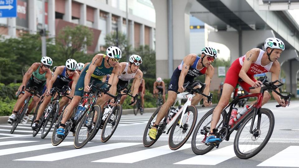 Des triathlètes font la course à vélo.