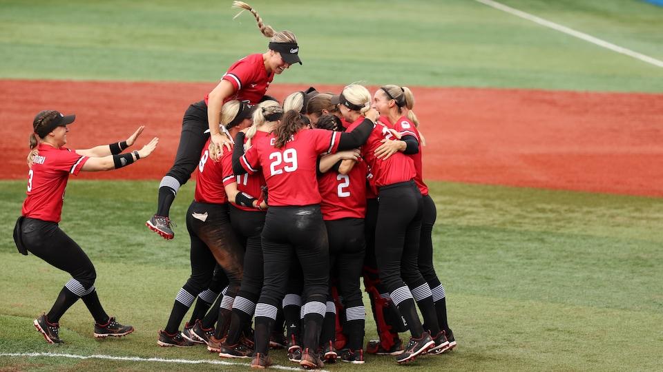 Les Canadiennes se serrent dans les bras au centre du terrain alors qu'une joueuse saute dans le groupe et qu'une autre arrive pour se joindre à elles.