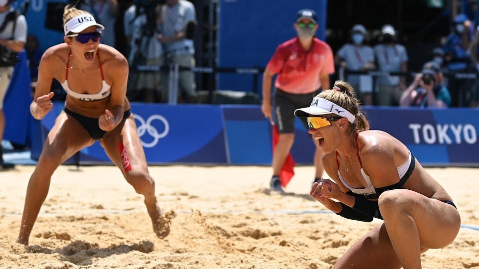 Deux joueuses de volleyball de plage crient et célèbrent leur victoire sur le terrain.