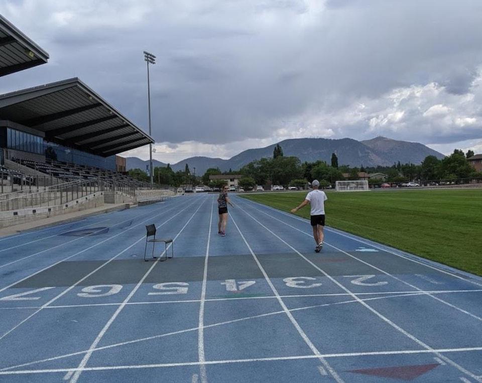 Elle s'entraîne en compagnie d'un homme sur une piste d'athlétisme extérieure désertée.