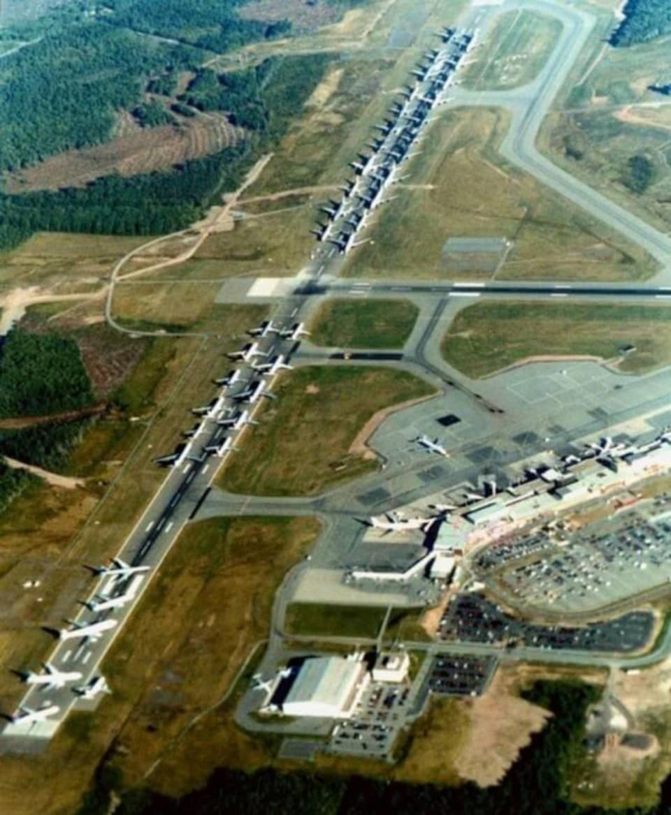 Photo aérienne de dizaines d'avions posés près les uns des autres sur la piste.