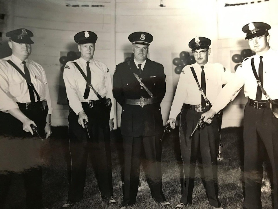 Cind policiers en uniforme, quatre ont des pistolets.