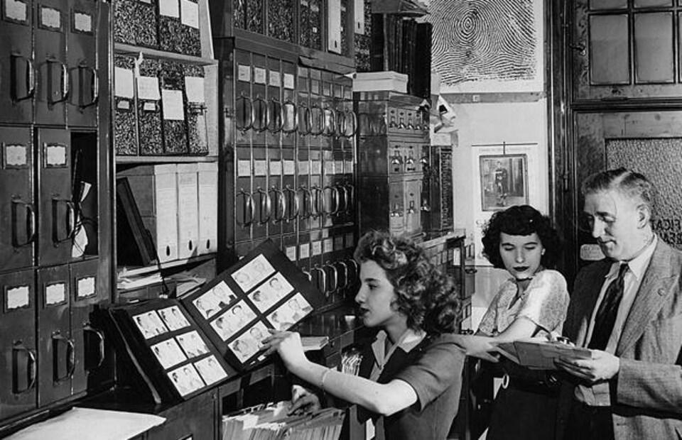 Photo d'archives : un homme et deux femmes dans un bureau rempli de classeurs.