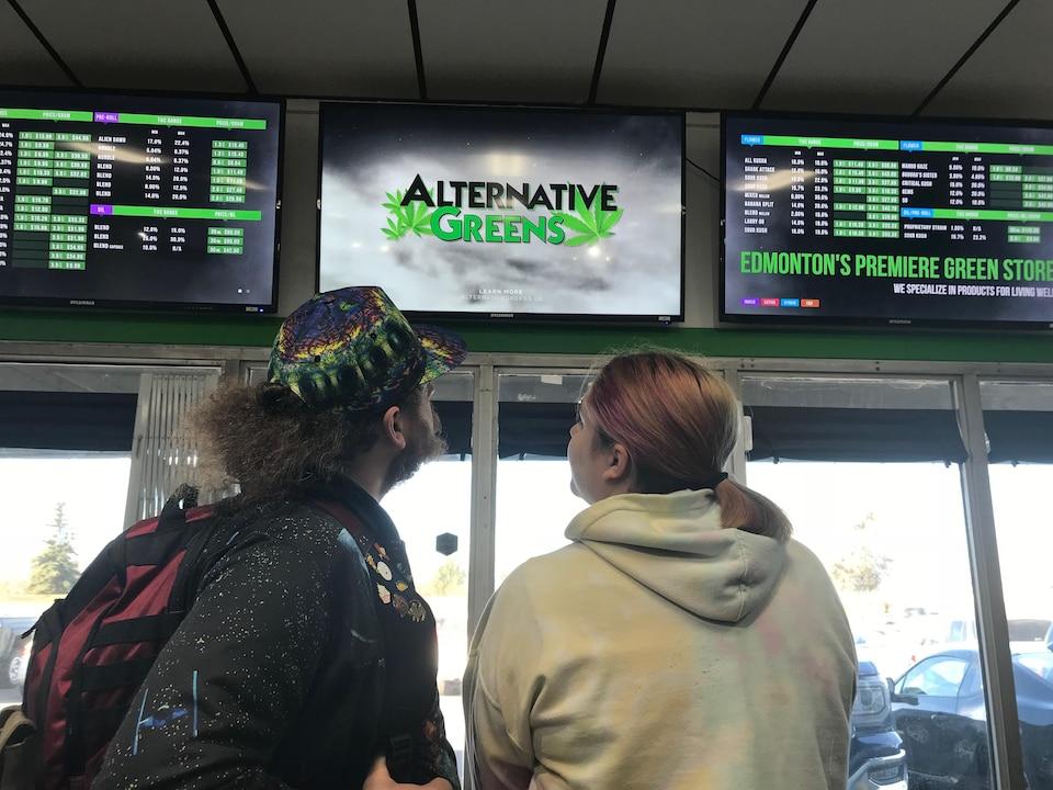 Un couple regarde des écrans où figurent les différentes sortes de cannabis offerts et leurs prix.