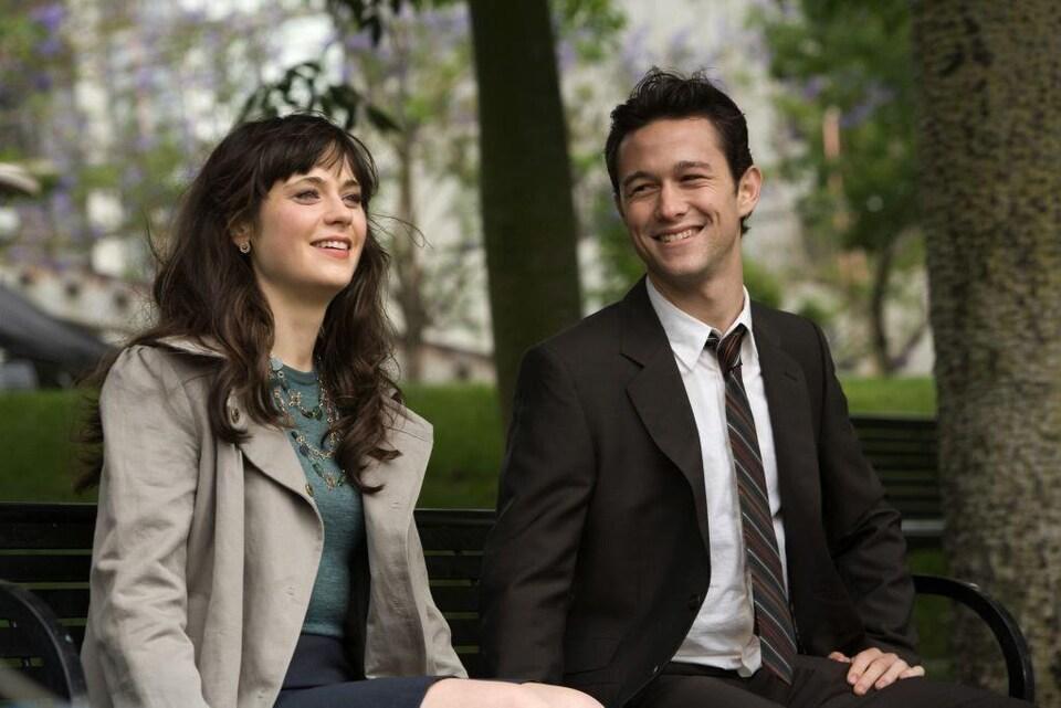 Les deux personnes sont assises sur un banc de parc entouré d'arbres.