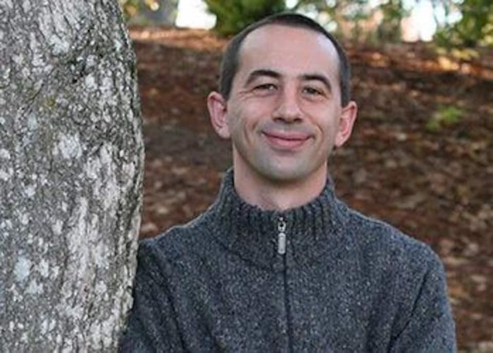 Une photo d'Aaron Weiskittel, professeur en foresterie à l'Université du Maine, adossé à un arbre.
