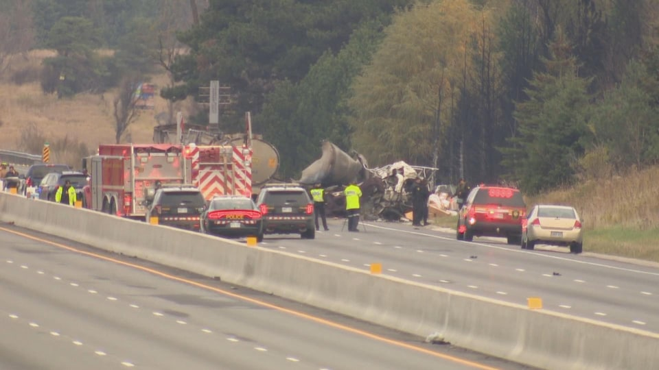 Photo d'un camion-citerne brûlé et noirci entouré de véhicules d'urgence