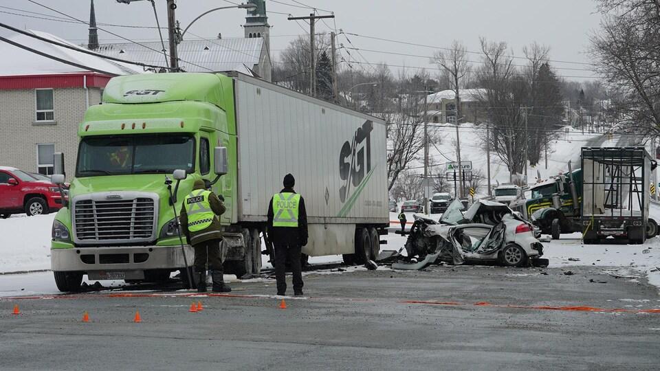 Des agents regardent une voiture accidentée à côté d'un camion