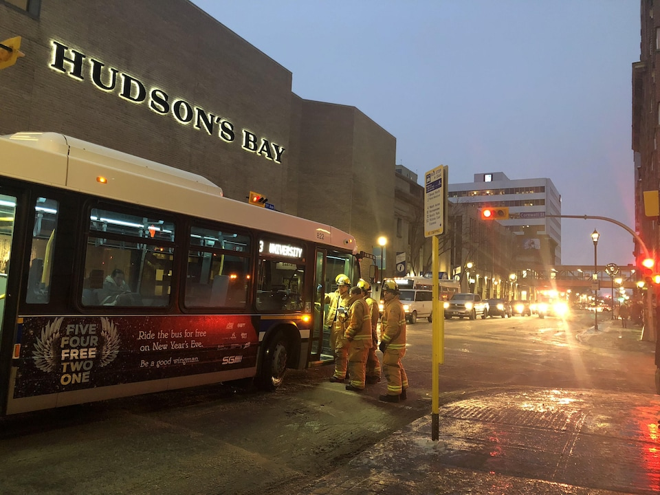 Un autobus arrêté dans la rue et des pompiers qui s'affèrent à vérifier que tout est ok.