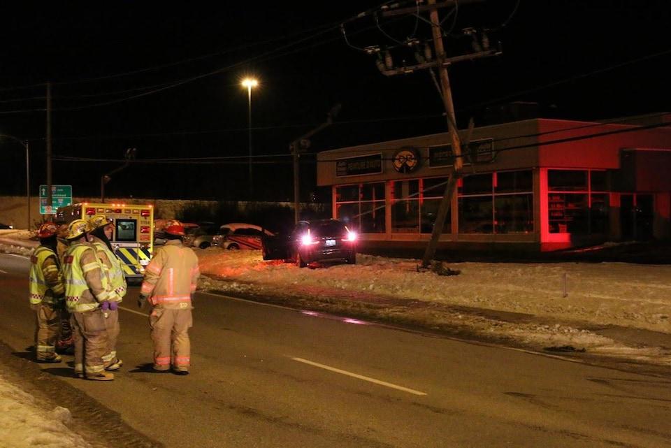 un groupe de cinq pompiers observe la voiture accidentée et un poteau électrique à moitié détruit.