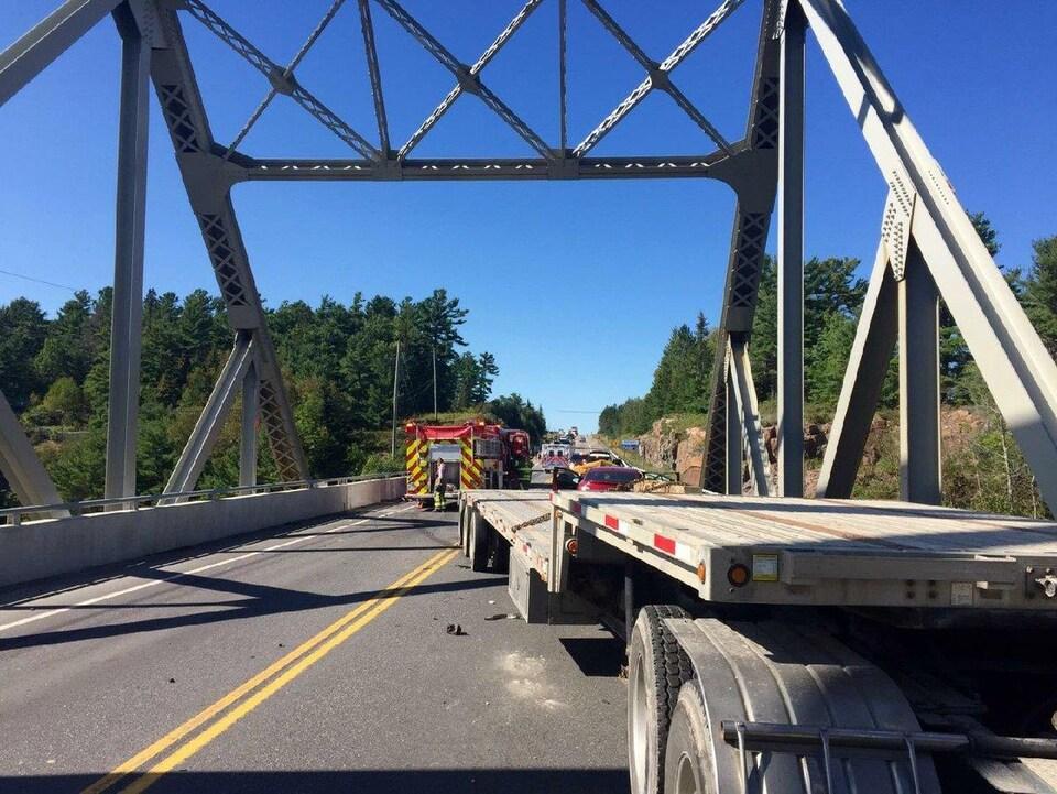 Un camion remorque en avant-plan sur un pont et des camions de pompiers.