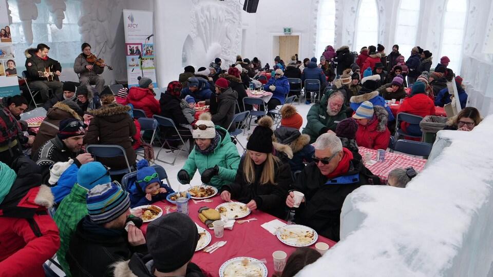 Des gens mangent à des tables dans un château de neige.